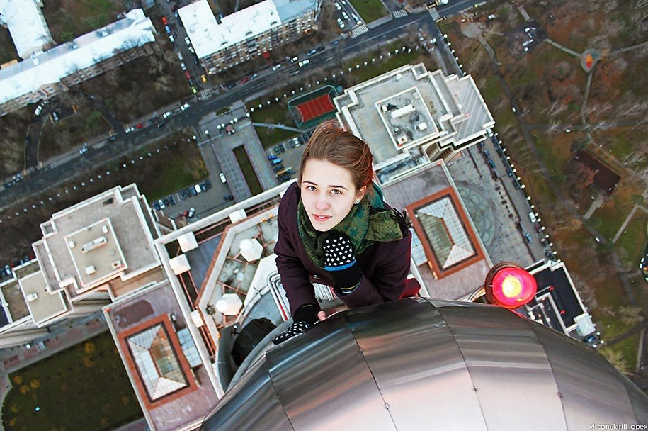 Woman taking a selfie on top of building. Picture by Flickr.